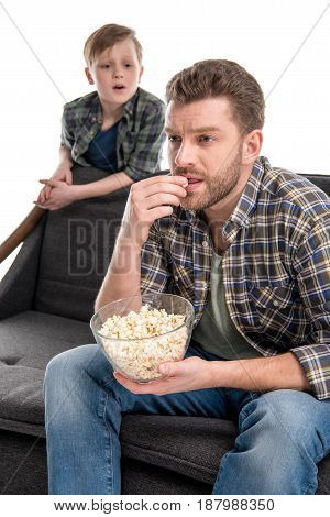 Son Talking With Father Sitting On Sofa And Eating Popcorn From Bowl, Family Problems Concept