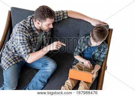 High Angle View Of Father Sitting On Sofa And Pointing With Finger At Son Using Digital Tablet, Fami