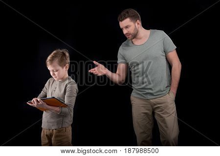 Father Gesturing And Looking At Son Using Digital Tablet, Family Problems Concept