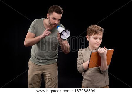Father With Megaphone Screaming At Little Son Using Digital Tablet, Family Problems Concept