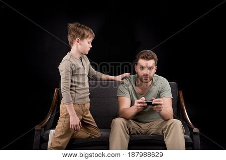 Boy Trying To Talk With Father Playing With Joystick, Family Problems Concept