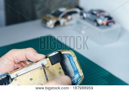 Hands of unrecognizable person handcrafting miniature auto with screwdriver.