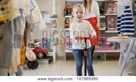 Portrait of a cute little girl who rides at a children's store.