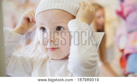 A little girl tries on a white hat in front of a mirror in a clothing store for children