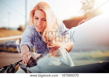 Young woman cleaning her car outdoors.Transportation self service care concept.