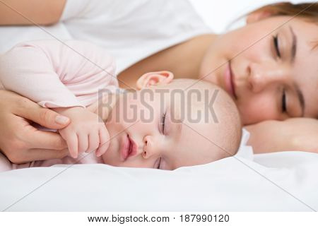 Young mother and her baby girl, sleeping in bed
