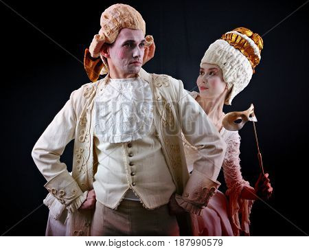 Man and woman in ancient costumes and white wigs