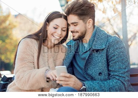 Happy couple making a selfie together outdoors.