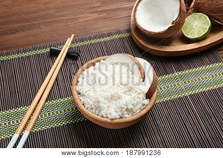 Wooden bowl with coconut rice on bamboo mat