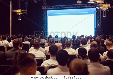 Audience at the conference hall. Speaker giving a talk in conference hall at business event. Business and Entrepreneurship concept. Lens focus on people in audience from rear.