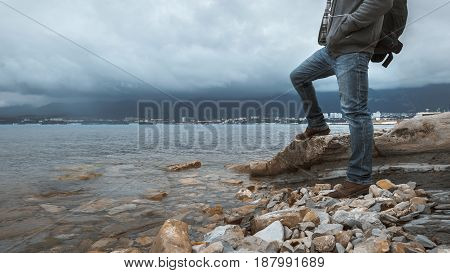 Man traveler with a backpack stands on the seashore against a background of clouds and a mountain range concept of hiking