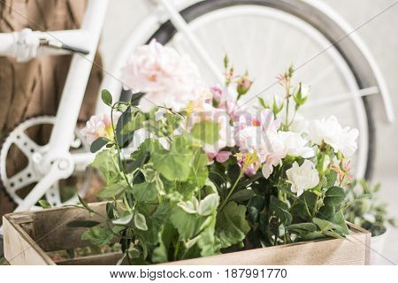 Reused white bycycle with baskets of flowers