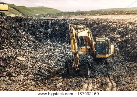 Heavy Duty Excavator Loader, Bulldozer Working In Garbage Dump. Recycling And Environmental Issues