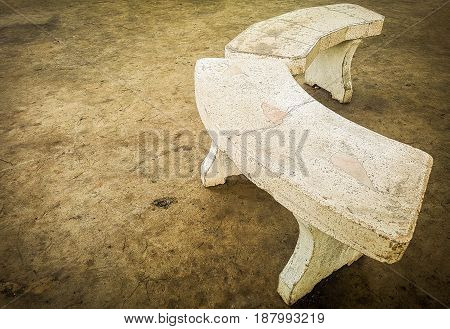 Old marble curved chair on concrete floor.