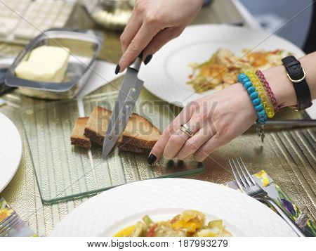 Female hands spreading butter on bread a messy breakfast table as a background.