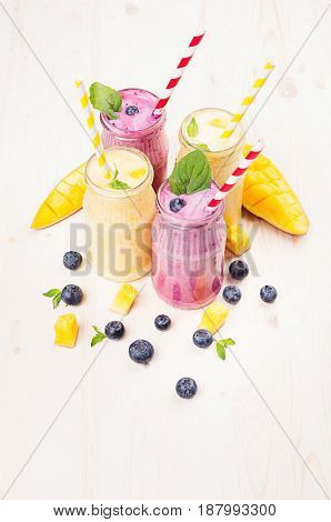 Freshly blended yellow and violet fruit smoothie in glass jars with straw mint leaves mango slices blueberry. Soft white wooden board background.