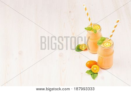 Freshly blended orange citrus kumquat fruit smoothie in glass jars with straw mint leaf cute ripe berry copy space. White wooden board background.