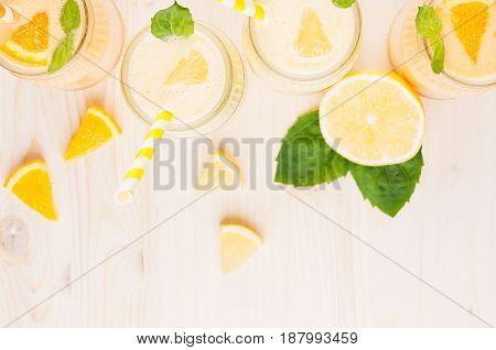 Orange and yellow lemon smoothie in glass jars with straw mint leaf slices orange and lemon top view. White wooden board background copy space.