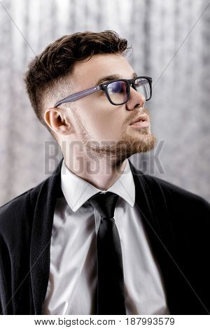 Portrait of a handsome young man with glasses and a white shirt on a grey background