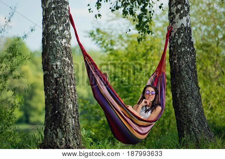 Portrait of young brunette girl in sunglasses is lies in a hammock.