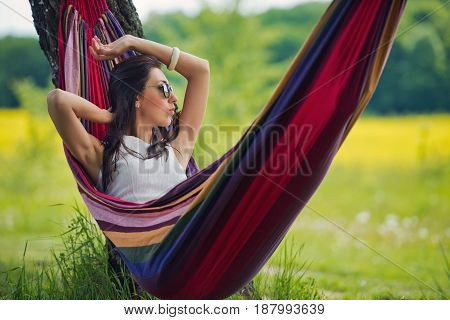 Young lovely brunette in sunglasses is lies in a hammock against the background of the field. Close-up.