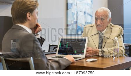 Young financial advisor sitting in front of laptop, consulting senior client with his investment strategy.