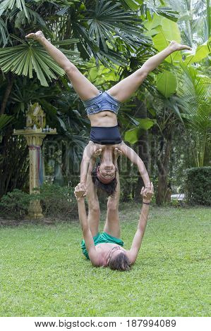 KOH PHANGAN THAILAND - NOVEMBER 13 2016 : Strong young couple doing acro yoga on green grass outdoors. Man and woman in park practising pair yoga poses.
