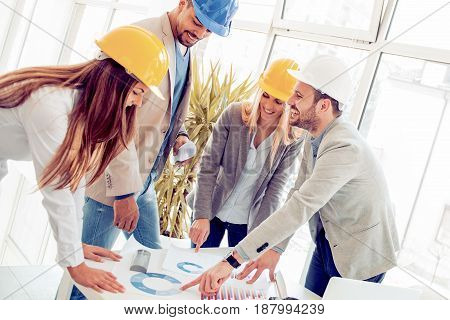 Group of architects correcting a construction plan in the office.