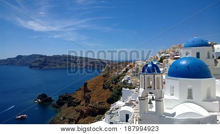 The popular town of Oia in Santorini - the top view on the beach, white houses and blue roofs