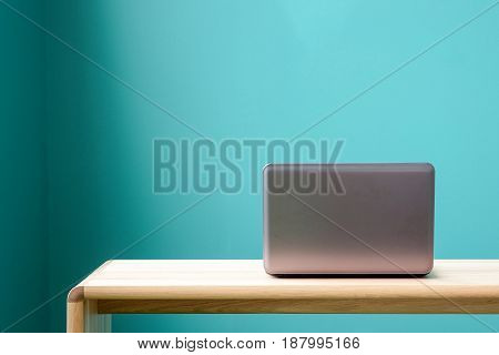 Computer notebook lap-top on office desk over green wall background with copy space