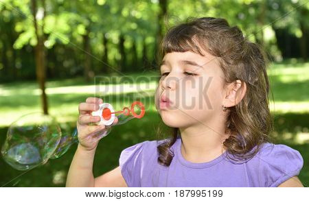 Cute young girl blowing the soap bubbles in the park