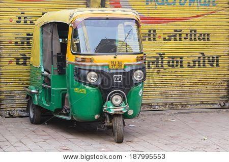 NEW DELHI INDIA - JANUARY 24 2017 : Auto rickshaw taxis on a road in New Delhi India. These iconic taxis have recently been fitted with CNG powered engines in an effort to reduce pollution