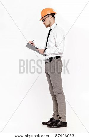 Young construction engineer in orange helmet writes in folder on a white background