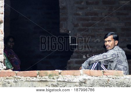 Delhi India september 3 2010: Young indian man sitting on a floor in ruined house.