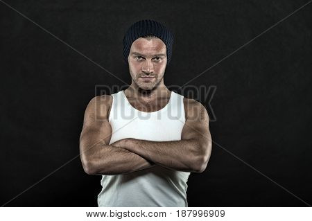 man or sexy guy with muscular hands in white vest and hat posing in studio on black background