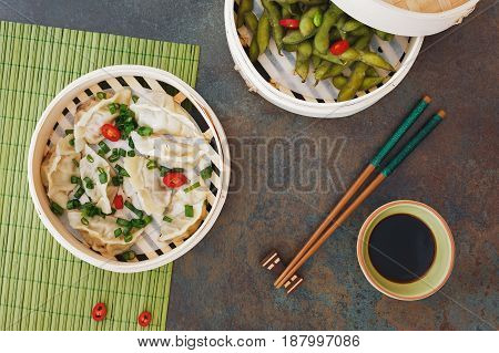 Streamed Gyoza (Jiaozi) and Edamame beans served warm with salt in bamboo steamer. Top view, blank space