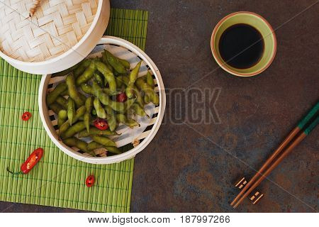 Spicy Edamame beans served warm with salt in bamboo steamer. Top view, blank space