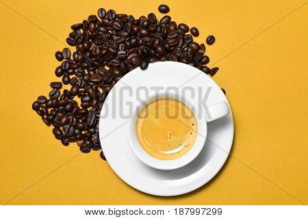 Hot espresso cup with coffee beans on brown background.