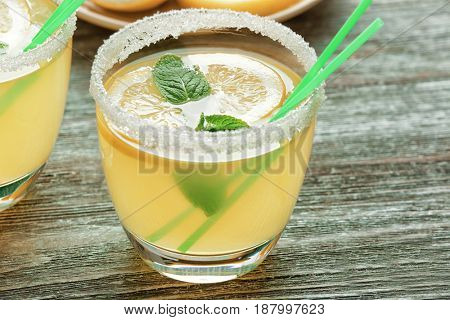 Glasses of lemon juice on wooden table
