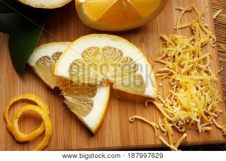 Cut lemons and zest on wooden board, closeup