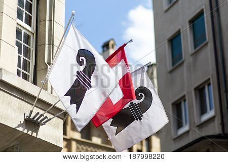 One Swiss flag in between two flags of the swiss canton of Basel