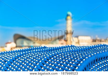 View from blue roofed wicker beach chair to landmarks of Warnemünde (Germany): lighthouse and shell-shaped teapot building at blurred background (copy space)