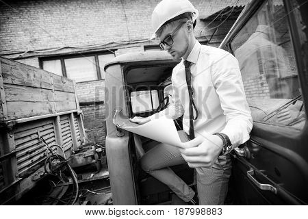 Engineer builder in a helmet holds drawings at the construction site