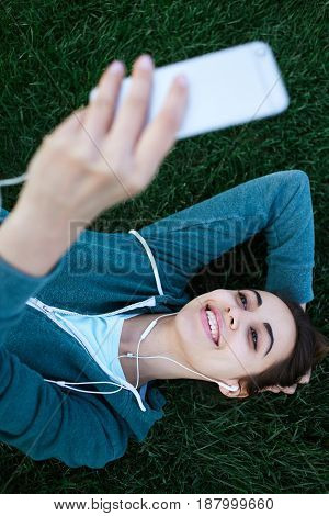 Portrait of young and sporty woman in sportswear lies with the smartphone and headphones on the grass outside at the park on green field on cloudy day, Dnipro, Ukraine. She is Lies on the green meadow between trees, listen music, making Video call or make