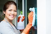asian housewife or housekeeper cleaning on glass window poster