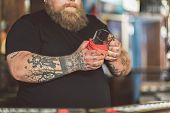 Boring job. Close-up of glass is in hands of fat bearded bartender. He wiping mug while standing at bar counter poster