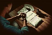 Top view image of the drug dealer was arrested in handcuffs has stack of banknote gun and package powder of drugs on wooden table Drugs concept in dark vintage color style poster