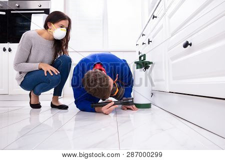Woman Looking At Male Pest Control Worker Spraying Pesticide On Wooden Cabinet