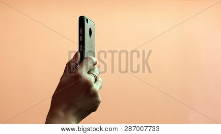 Photo or video shooting on a mobile phone. The hand of a girl with a gold ring on her finger holds a smartphone in the mode of selfie or sequential shooting. Pink background. Copy space. Close-up. Selective focus. poster