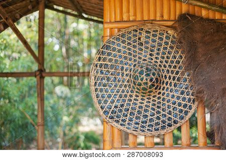 Chinese Straw Hat Hanging On A Bamboo Wall In The Countryside, China